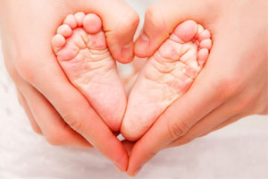 Baby feet in mother hands. Tiny Newborn Baby s feet on female Heart Shaped hands closeup. Mom and her Child. Happy Family concept. Beautiful conceptual image of Maternity